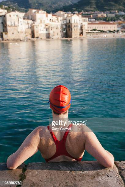 female swimmer looking out to sea - 人の背中 ストックフォトと画像