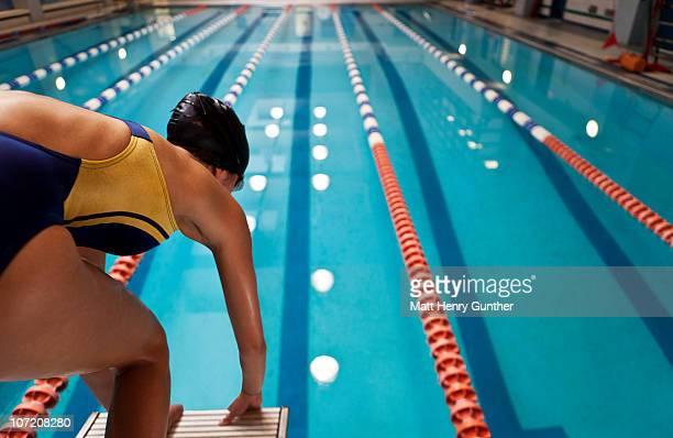 Female swimmer on block ready to dive in