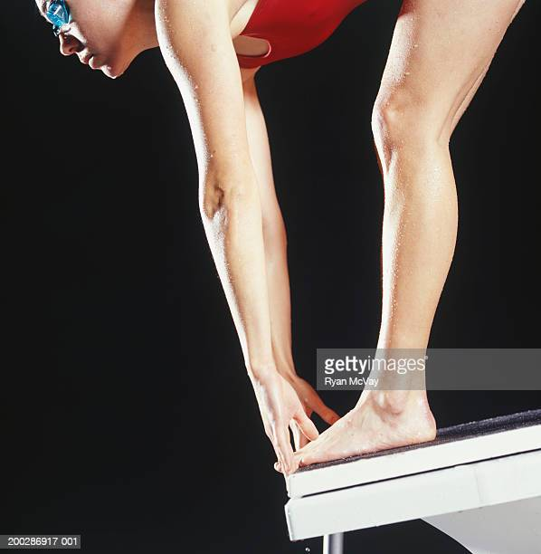 Female swimmer preparing to dive off starting block, close-up, studio shot