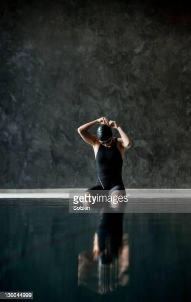 female swimmer sitting on pool edge fixing goggles