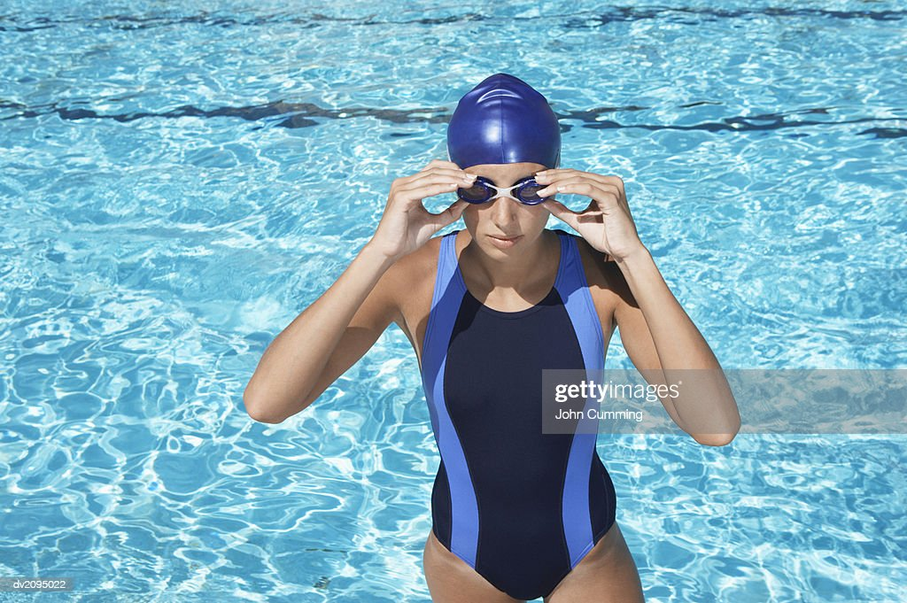 Female Swimmer Wearing a Swimming Cap and Goggles in Front of a Swimming Pool : Stock Photo