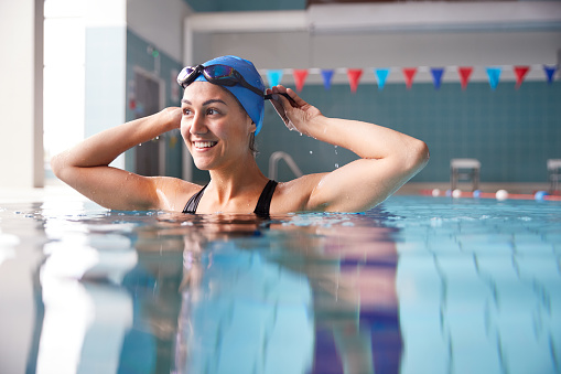 Female Swimmer Wearing Hat And Goggles Training In Swimming Pool 1167733434