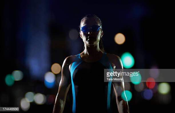 female swimmer with city lights