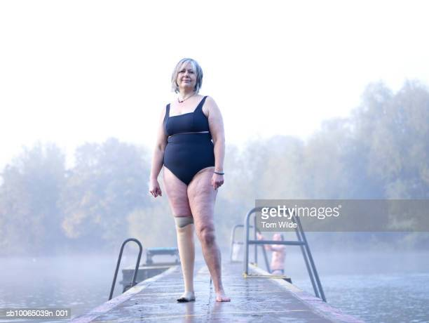 Female swimmer with prosthetic leg standing on jetty, portrait