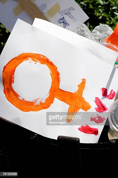 Female symbol and disposable cups in a garbage bin