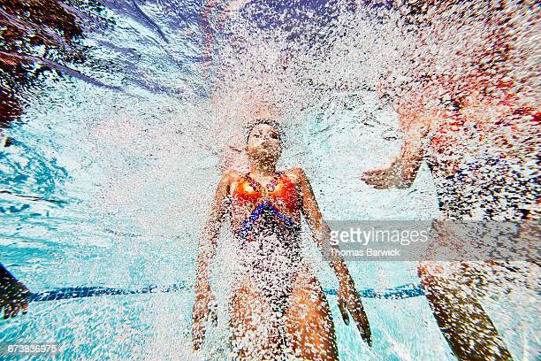 Female synchronized swimmer swimming to surface