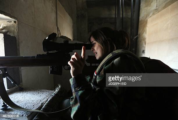 A female Syrian sniper from the Republican Guard commando battalion aims fire during clashes with rebels in the restive Jobar area in eastern...