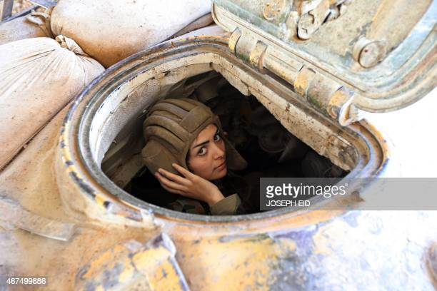 A female Syrian soldier from the Republican Guard commando battalion drives a tank during clashes with rebels in the restive Jobar area in eastern...