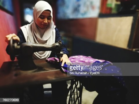 Female Tailor In Hijab Using Sewing Machine