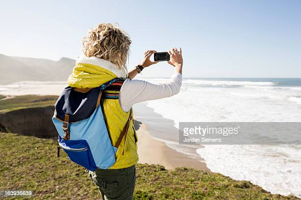 A female taking an ipone picture.
