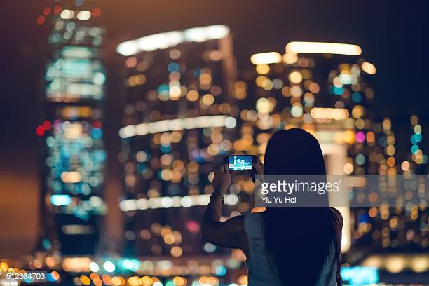 Female taking photo of city with smartphone