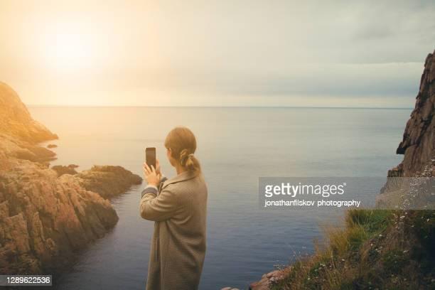 スマートフォンで写真を撮る女性 - モバイル撮影 ストックフォトと画像