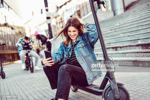 female taking selfie with electric scooter while her friends make stunts - electric scooter stock pictures, royalty-free photos & images