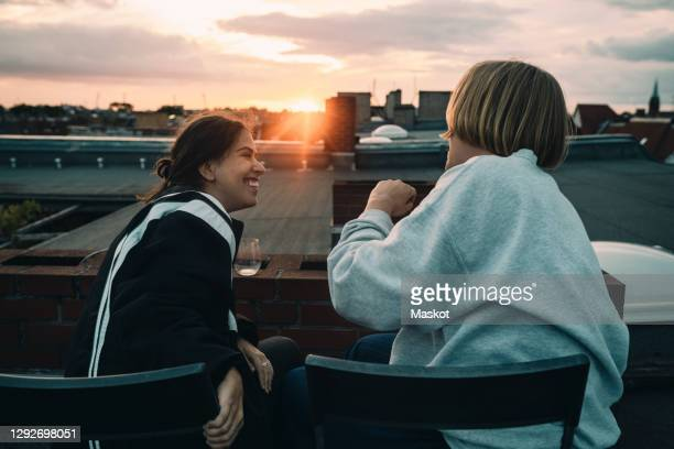 female talking to smiling friend while enjoying on building terrace - two people stock pictures, royalty-free photos & images