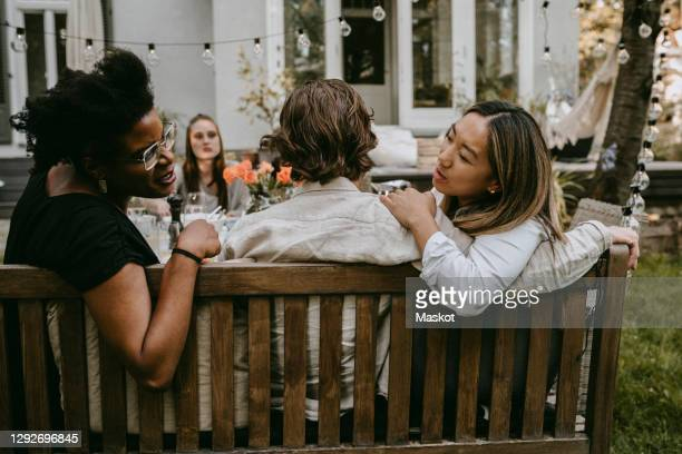 female talking to young friend behind partner during social gathering - hanging stock pictures, royalty-free photos & images