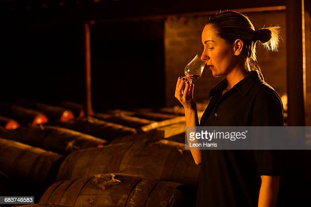 Female taster smelling whisky in glass at whisky distillery