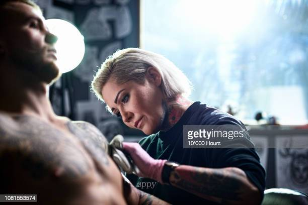 female tattooist applying tattoo to male customer - tatuagem imagens e fotografias de stock