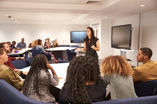 Female teacher addressing university students in a classroom 597959356