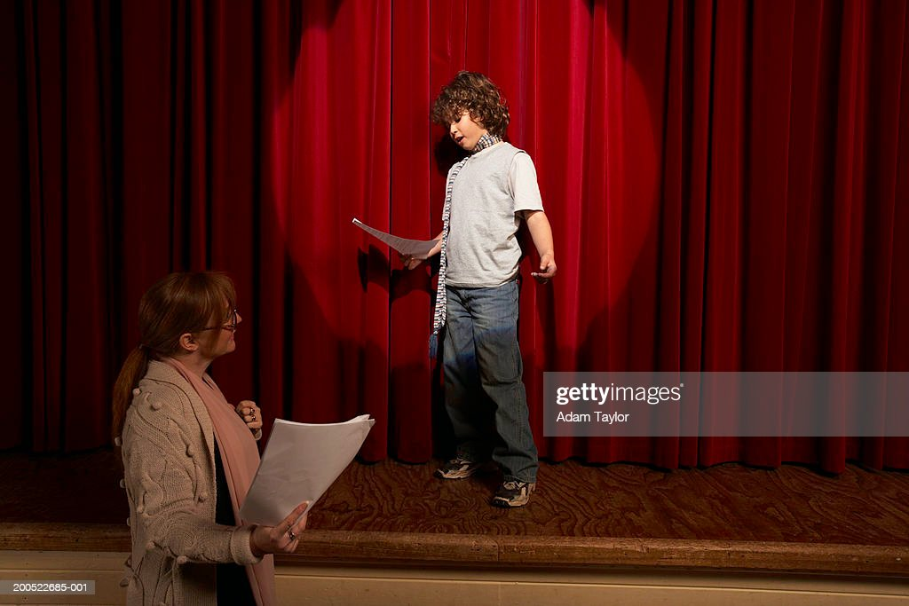 Female teacher and boy (10-12) standing on stage rehearsing : Stockfoto
