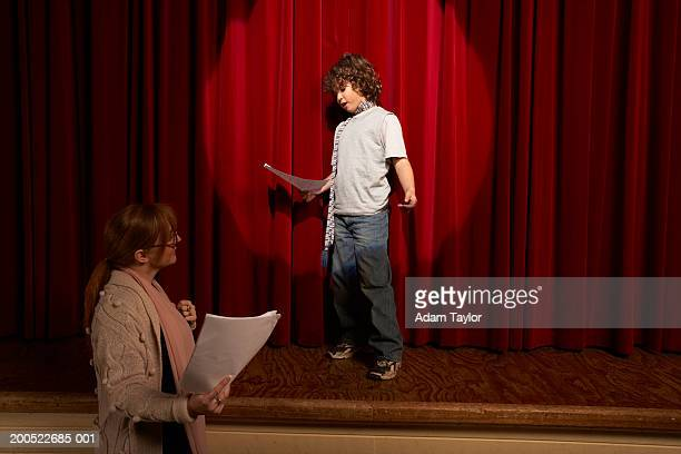 female teacher and boy (10-12) standing on stage rehearsing - acting stock pictures, royalty-free photos & images
