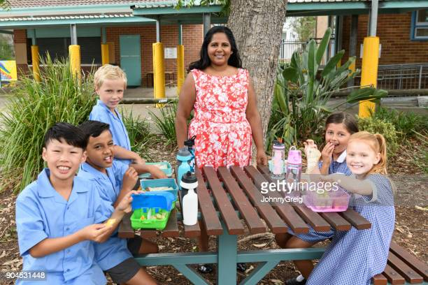 Female teacher and group of school children enjoying lunch outside in playground