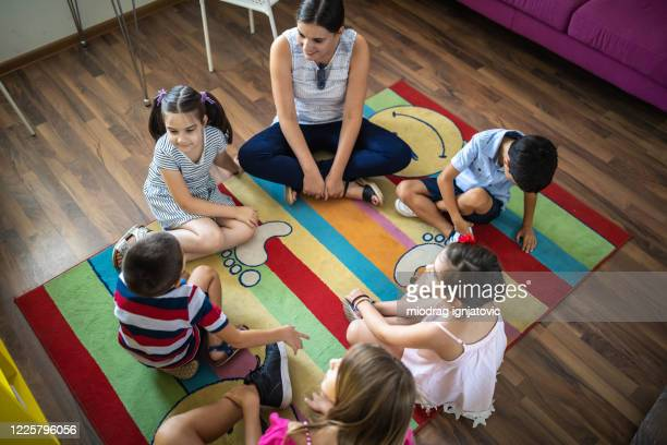 female teacher and kids sitting at floor at daycare - preschool child stock pictures, royalty-free photos & images