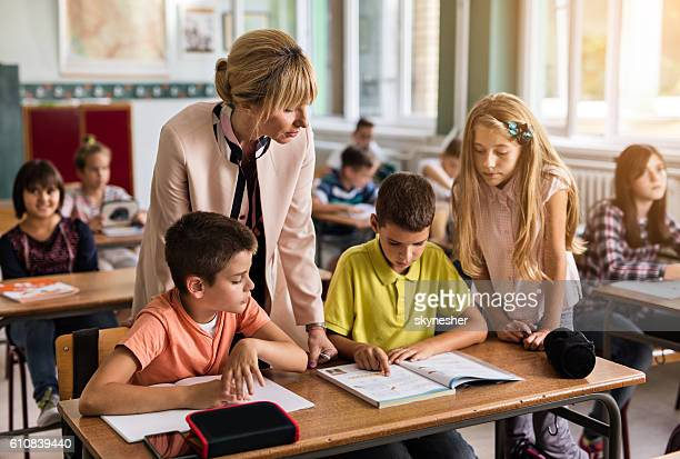 female teacher assisting to elementary students in the classroom. - workbook stock photos and pictures