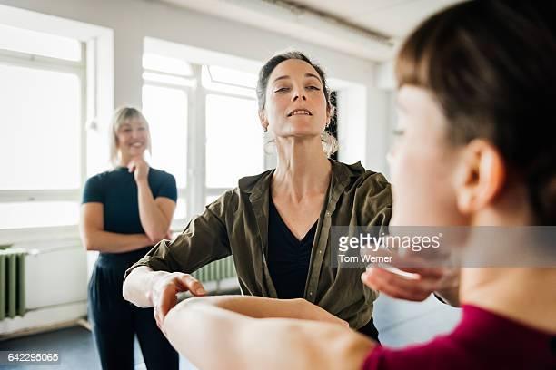 female teacher correcting dancer - perfektion stock-fotos und bilder