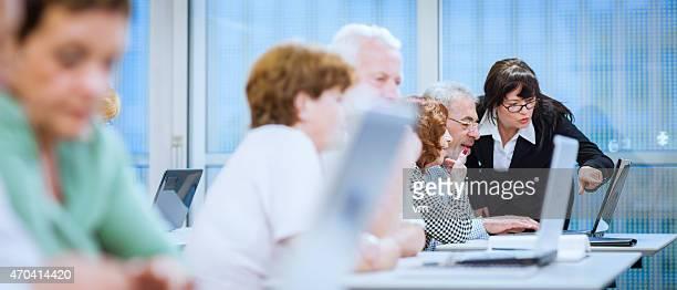 Female Teacher Explaining New Computer Technology to Senior Man