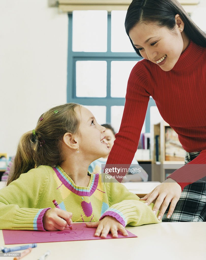 Female Teacher Helping a Primary Schoolgirl in a Classroom : Stock Photo