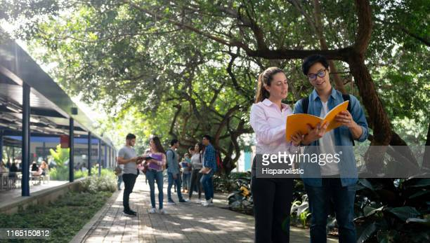 female teacher helping an exchange student at the university campus both looking at a notebook while she explains something - hispanolistic stock photos and pictures