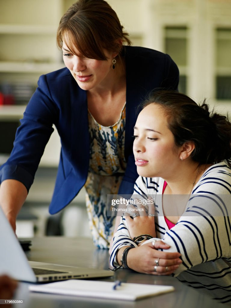Female teacher helping student working on laptop : Stock Photo
