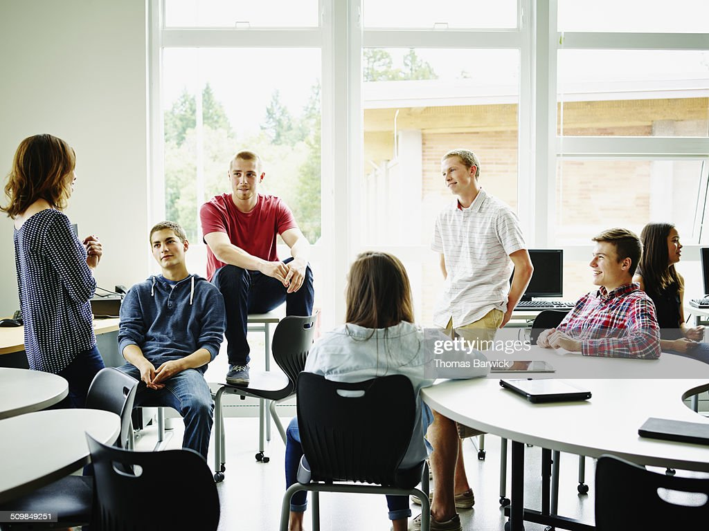 Female teacher in class discussion with students : Stock Photo