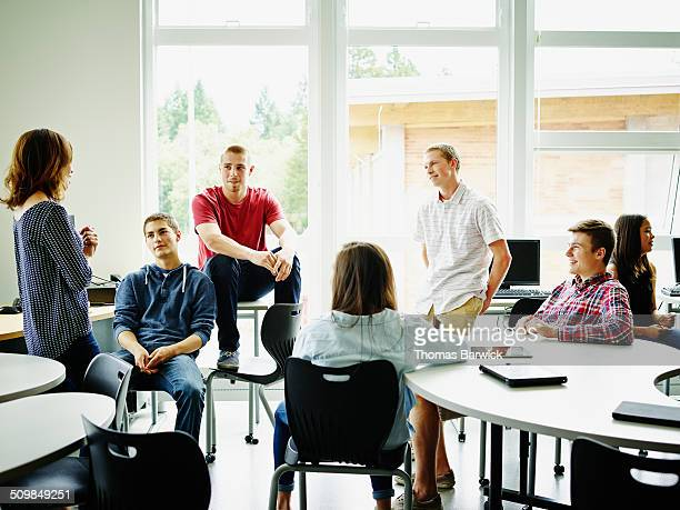Female teacher in class discussion with students