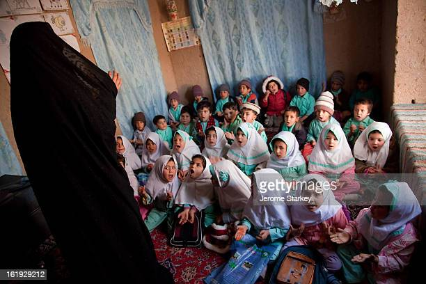 Female teacher leads pre-school children in song at a community-run childcare class outside Herat, Nov 29, 2011. There are more than 800 children...