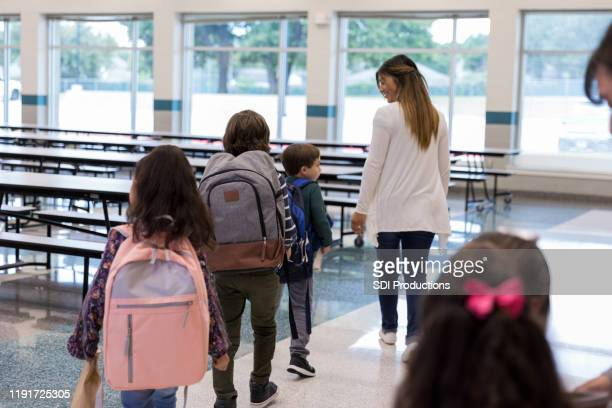 female teacher leads students into school cafeteria - following moving activity stock pictures, royalty-free photos & images