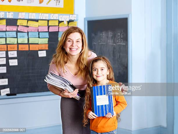 Female teacher posing with school girl (6-7) in classroom, portrait