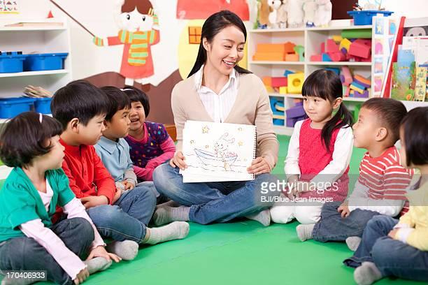 Female teacher showing kindergarten children picture book