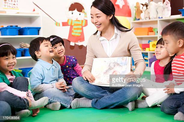 female teacher showing kindergarten children picture book - storyteller stock pictures, royalty-free photos & images