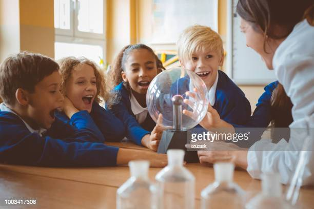 female teacher showing plasma ball during lesson at school - education stock pictures, royalty-free photos & images