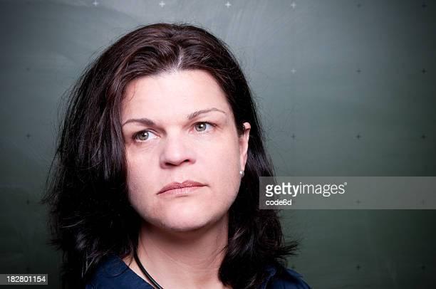 Profesor mujer de pie en pizarra, mirando triste, espacio de copia