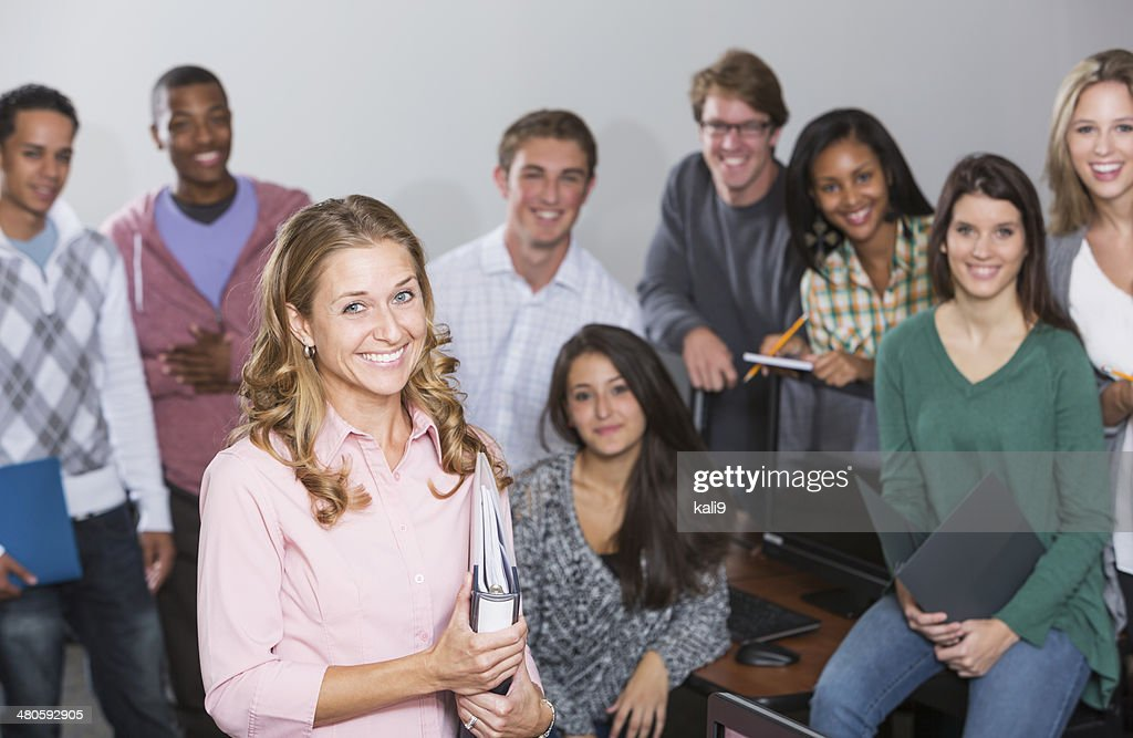 Female teacher standing in front of group of students : Stock Photo