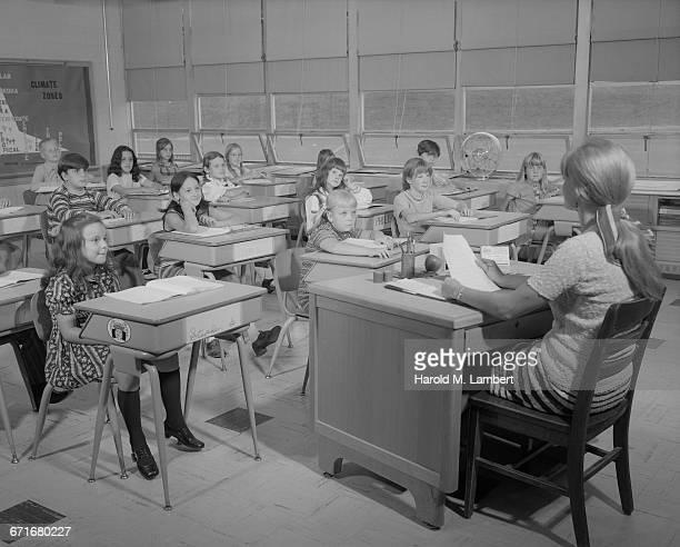 ' Female Teacher Teaching In Classroom, Students Listening'