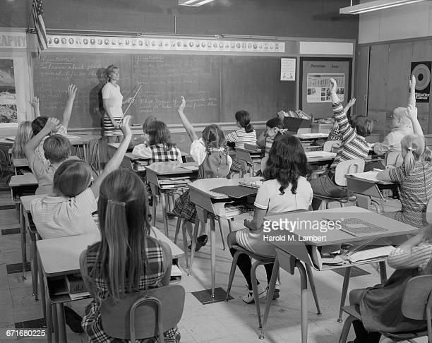 ' Female Teacher Teaching In Classroom, Students Raising Hand'