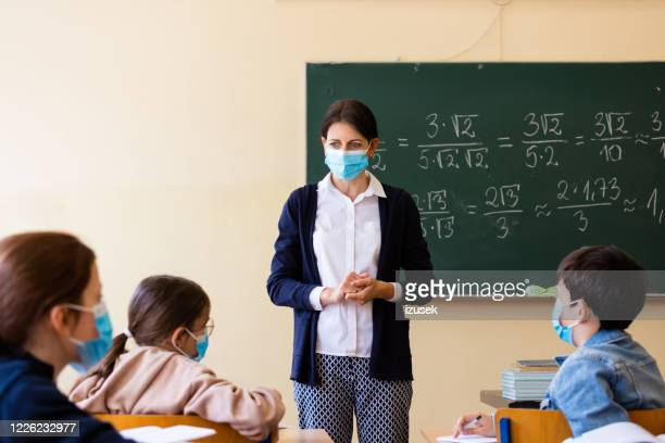 female teacher teaching mathematics at school during covid-19 - teacher stock pictures, royalty-free photos & images