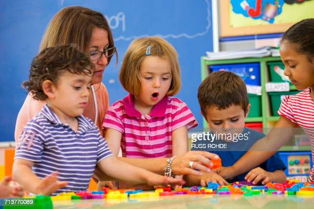 Female teacher with preschool boys and girls learning alphabet in classroom