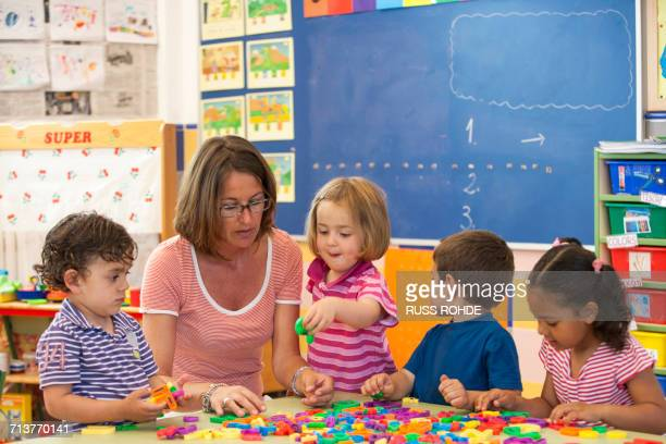 female teacher with preschool boys and girls learning alphabet in classroom - nursery school child stock pictures, royalty-free photos & images