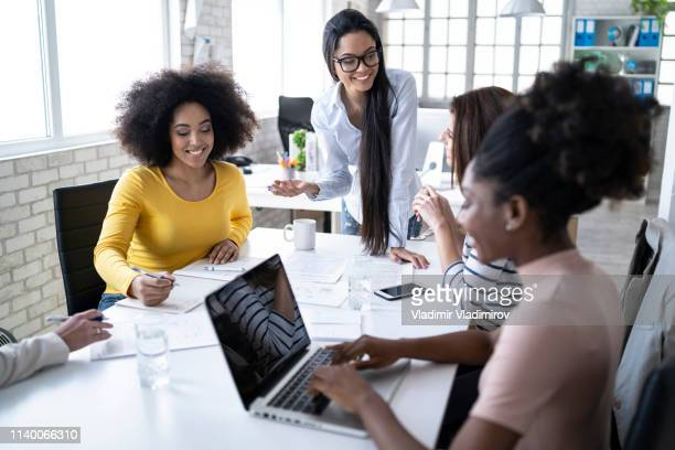 female team discussing ideas and using laptop at work - employee engagement stock pictures, royalty-free photos & images