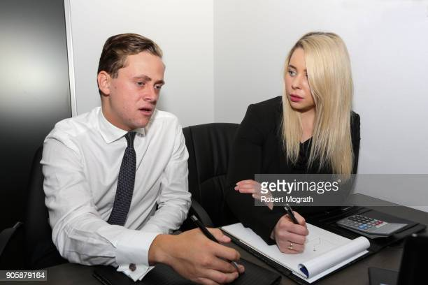 Female team leader and male team member discuss strategy and take notes.