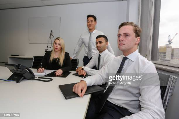 Female team leader and takes notes while three male team members listen to client's presentation.